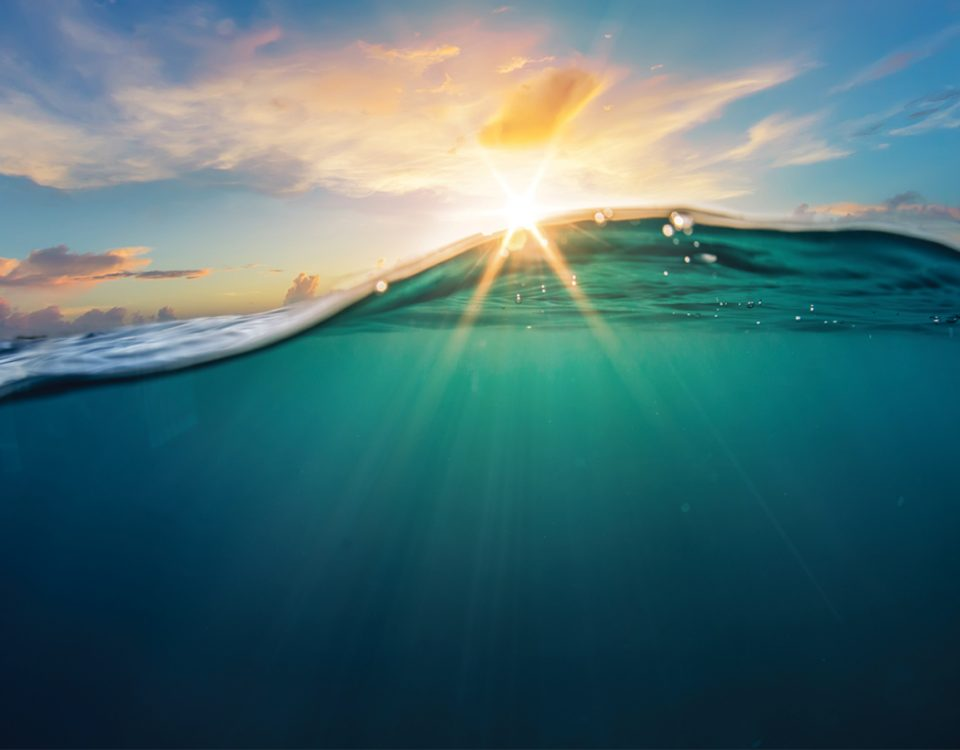 Wave of turquoise water backlit by the sun
